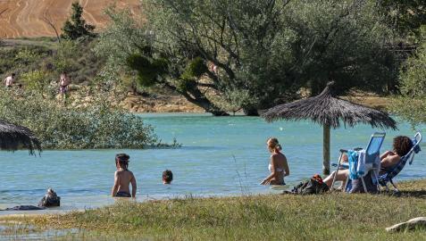 Una familia descansa en la zona de baño de Lerate en el embalse de Alloz mientras los niños se bañan.