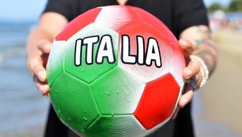 Un aficionado sujeta yun balón con los colores de Italia en la playa de Castiglione della Pescaia