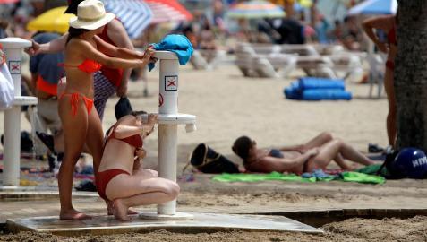 Dos mujeres tratan de refrescarse en los lavapaies de la playa de El Postiguet de Alicante