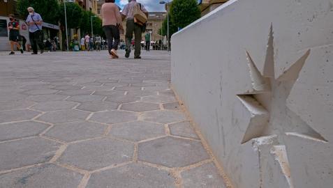 El suelo con adoquines hexagonales y  los bancos-jardineras con la estrella de la ciudad en una imagen de la calle San Andrés