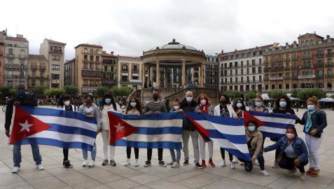Un grupo de ciudadanos cubanos despliega las banderas del país en la Plaza del Castillo de Pamplona