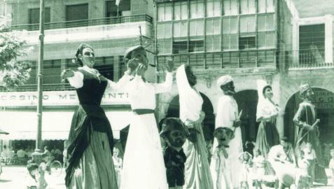 Fotografía de 1954 con los gigantes María Puy y Andrés bailando en la plaza de los Fueros junto al resto de figuras de la comparsa, los reyes moros, Juan de Labrit y Blanca de Navarra.