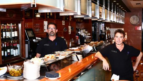 Eduardo Zubieta posa en la barra del bar StickBol repleta de pinchos junto a otro camarero