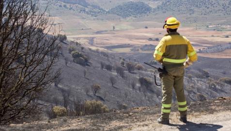 Un miembro de los Servicios de Emergencia trabaja este lunes en las labores de extinción del incendio forestal en el Monte Yerga
