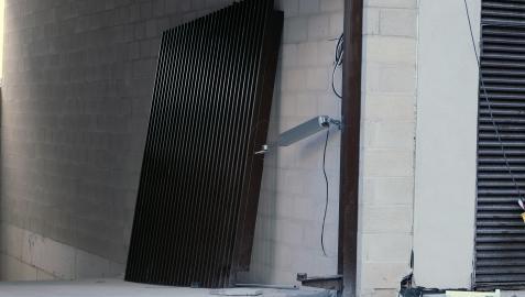 Puerta metálica bajo la que quedó atrapado el trabajador.