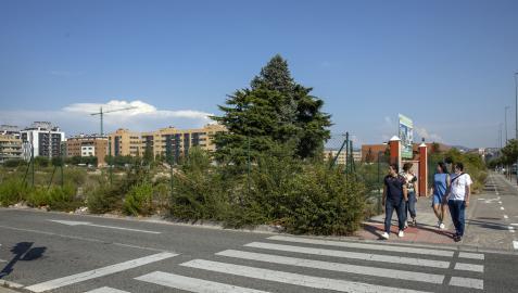 Un grupo de personas pasa por la acera de la avenida Gupúzcoa junto al solar que cobijará un cubo comercial y viviendas