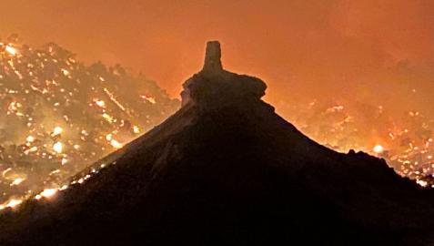 El cerro del castillo de Peñaflor con las llamas del incendio al fondo