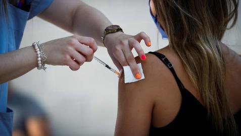 Una sanitaria vacuna a una joven