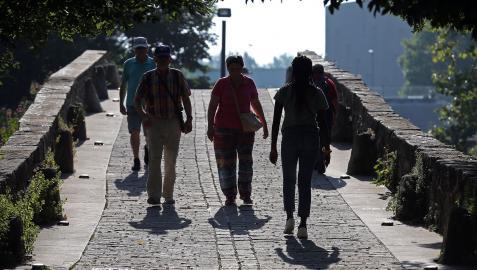 Varias personas pasean por el puente de San Pedro.