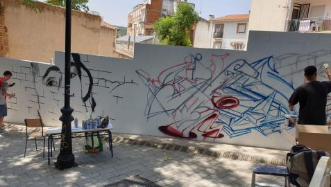 Varios grafiteros decoran una de las fachadas de la localidad madrileña de San Martín de Valdeiglesias.