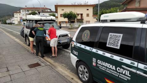 Un agente de la Guardia Civil atiende a dos peregrinos