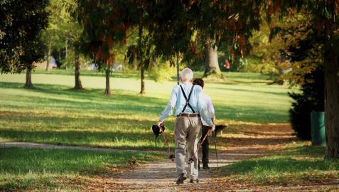 Dos personas mayores paseando en un parque