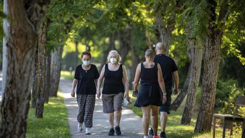 Varias personas caminan por el Paseo del Arga