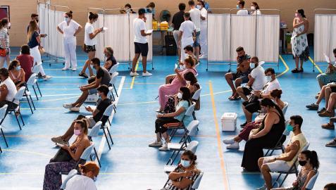 Jóvenes esperan tras ser vacunados en el pabellón municipal de Espartinas (Sevilla)
