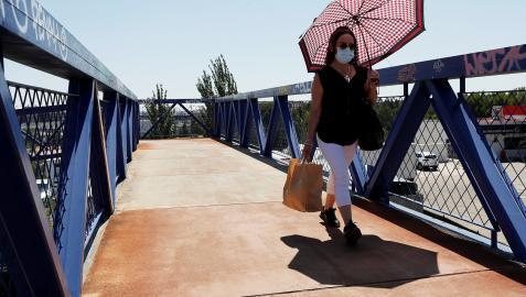 Una mujer con mascarilla se protege del sol cuando cruza por una pasarela en Madrid