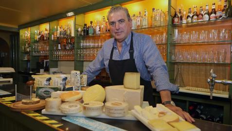 Aitor Otazu Larrauri posa en la barra del bar Savoy con varias tablas de queso