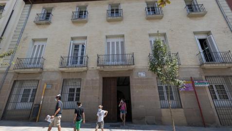 Varias personas pasean ante la fachada de la biblioteca de Tudela, situada en la calle Herrerías