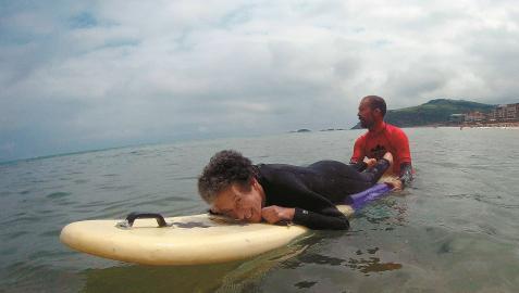 Marian Cano, tumbada sobre una tabla de surf, con un monitor de 'MOOR Surf Eskola', en Zarautz (Guipúzcoa), el pasado 3 de julio