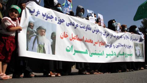 Mujeres afganas sostienen una pancarta con fotografías del ex comandante muyahidín Ismail Khan, quien junto con su milicia armada está luchando contra los talibanes