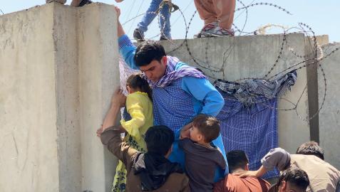 Un padre ayuda a sus hijos a superar un muro para entrar en el aeropuerto de Kabul