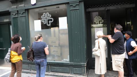 Varias personas comprueban los números, este lunes, en la sede de Cáritas en la calle San Antón