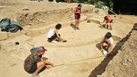 Personas voluntarias toman medidas del ábside hallado durante los trabajos de excavación