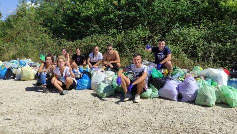 Los ocho jóvenes zizurtarras posan satisfechos con tras dejar despejado el tramo del Camino de Santiago entre Zizur y Galar.