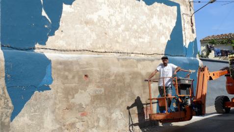 El pamplonés Gabriel Coca, junto al mural que realizó en la calle Rey de Cintruénigo.