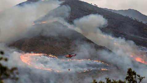 Un helicópetero trabaja en las labores de extinción del incendio de Sierra Bermeja