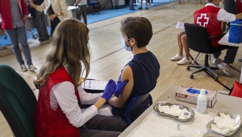 Una voluntaria de Cruz Roja administra una dosis de la vacuna contra el Covid-19 a un estudiante universitario en el campus de Ciudad Universitaria