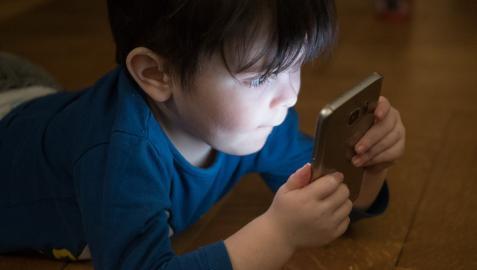 Imagen de archivo de un niño usando un teléfono móvil.