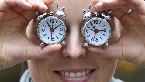 Una mujer cubre sus ojos con dos relojes