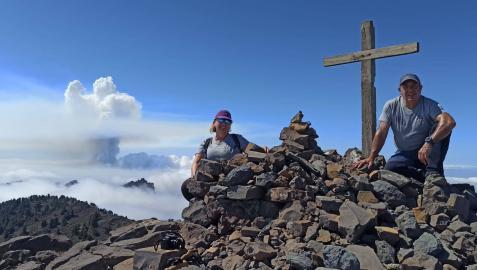 Mikel Aznárez y Malu Bojan Arregui, ayer al mediodía en La Palma, en el Pico de la Nieve. Al fondo, la columna de humo y vapor del volcán