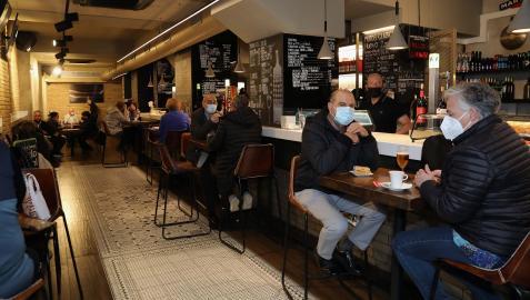 Mesas y sillas altas en el bar Río de Pamplona, como alternativa a la imposibilidad de consumir de pie en la barra