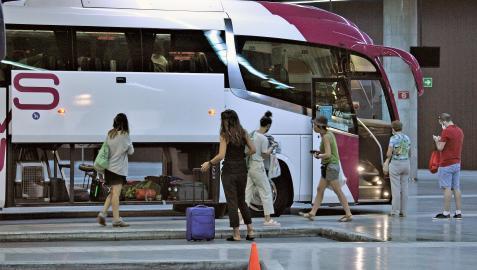 Varios viajeros esperan para subir a un autobús interurbano
