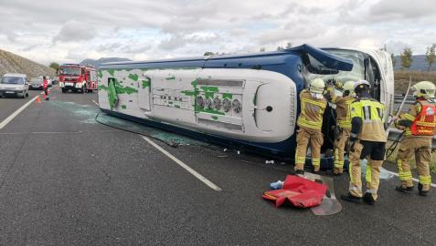 Bomberos atienden a los afectados en el accidente con un autobús volcado.