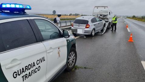 Imagen de un coche de la Guardia Civil junto al vehículo implicado en el accidente.