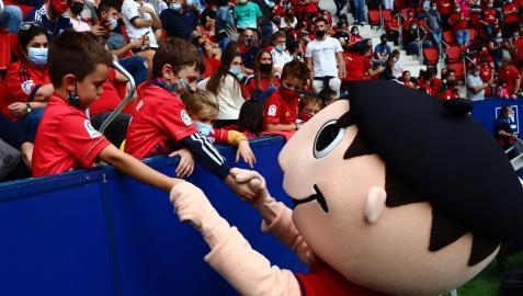 La mascota Rojillo saluda a dos jóvenes aficionados