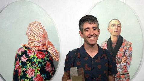 David Anocibar recogiendo el premio con el díptico premiado detrás