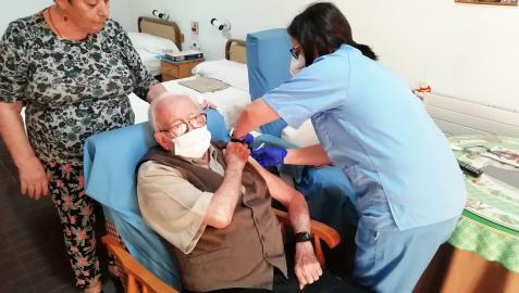 Una sanitaria pone una vacuna a un anciano en una residencia de Andalucía
