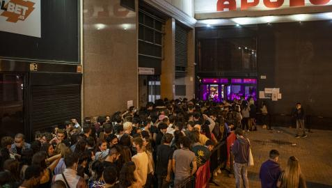 Grupos de jóvenes en las inmediaciones de un local de ocio nocturno la misma noche en que entra en vigor la reapertura en interiores a medianoche en Barcelona
