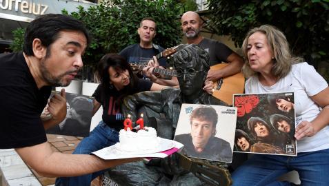 El periodista Adolfo Iglesias, autor del libro 'Juan y John, el profesor y Lennon en Almería para siempre' celebra junto a varios aficionados a los Beatles, el 81 cumpleaños del John Lennon, frente a la estatua del musico inglés en Almería.