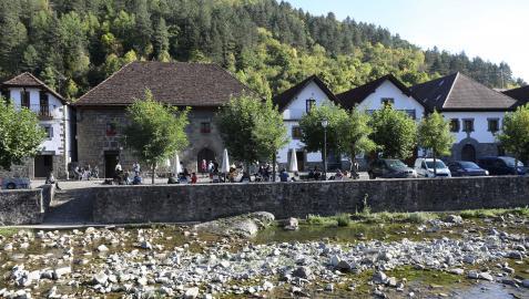 Turistas disfrutan del buen tiempo en las terrazas de Ochagavia junto al río Anduña