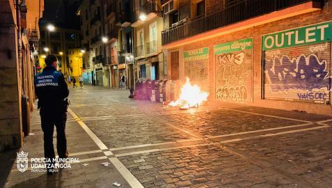 Un agente de la Policía Municipal ante unos contenedores ardiendo este fin de semana en el Casco Viejo de Pamplona