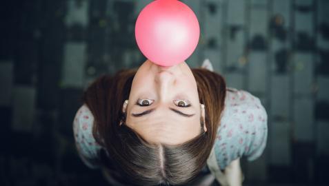 Una joven hace una pompa con un chicle