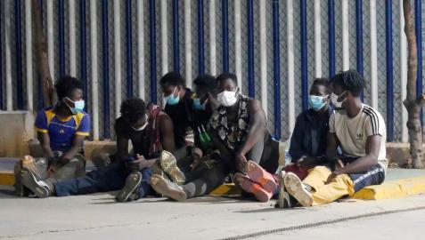 Varios migrantes de origen subsahariano permanecen bajo vigilancia policial tras acceder a Melilla saltando el perímetro fronterizo entre España y Marruecos