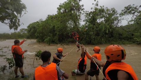 Equipos de rescate ayudan a una persona a pasar sobre un río en la provincia filipina de Gonzaga