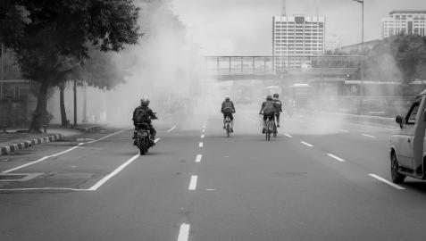 Varias personas circulan en moto o bicicleta entre el humo en una ciudad