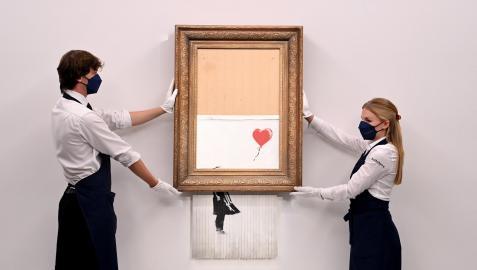 Empleados de la galería muestran la obra de Banksy 'Love is in the Bin'