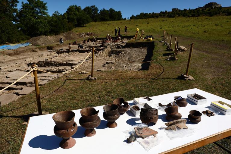 En primer plano, algunas de las vasijas encontradas en Irulegi. En segundo término, estado de la intervención arqueológica que financia Aranguren y dirige Aranzadi